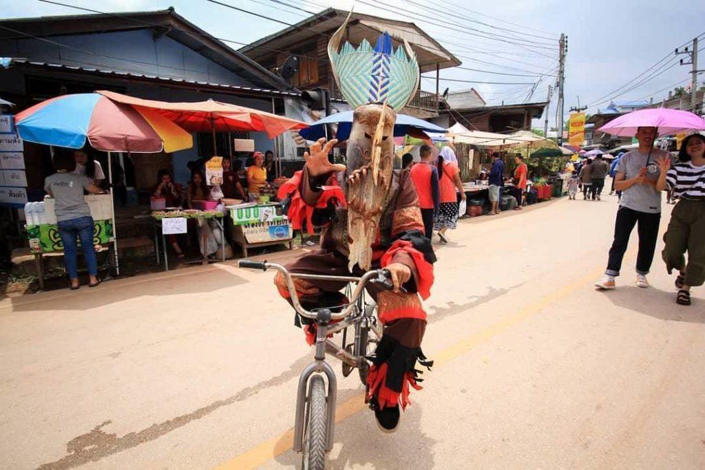 Phi ta khon et son masque faisant du velo